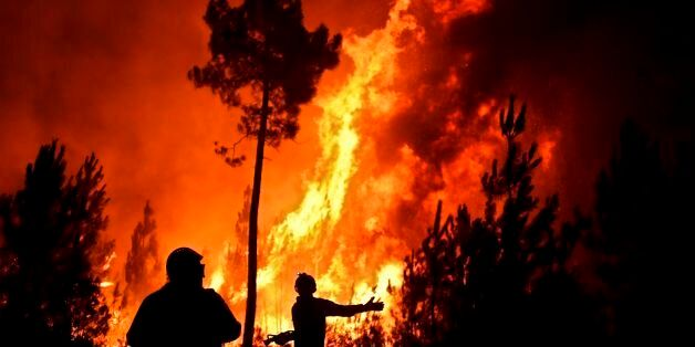 Firefighters tackle a wildfire at Vale de Abelha village in Macao, on August 16, 2017. / AFP PHOTO /...