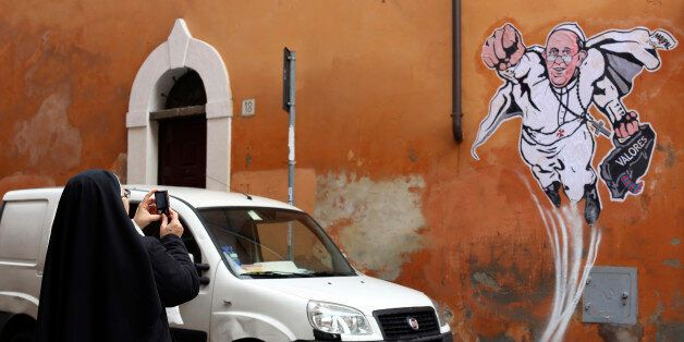 A nun takes a picture of a large drawing of Pope Francis depicting him as a superhero on a wall near...