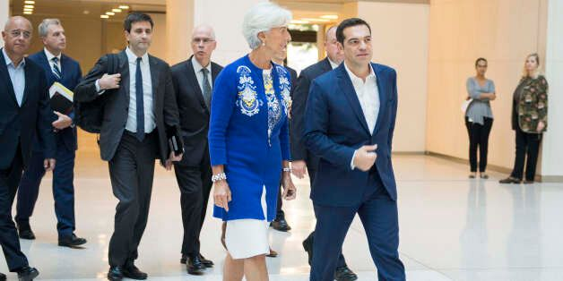 Greek Prime Minister Alexis Tsipras (R) talks with International Monetary Fund (IMF) Managing Director...