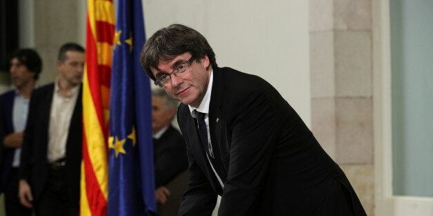 Catalan President Carles Puigdemont signs a declaration of independence at the Catalan regional parliament...