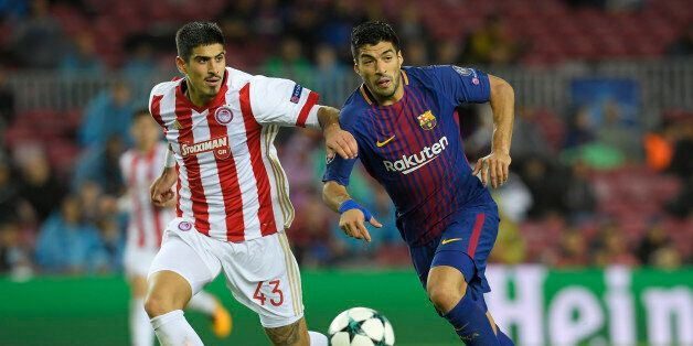 Barcelona's Uruguayan forward Luis Suarez (R) vies with Olympiacos' Greek defender Dimitris Nikolaou...