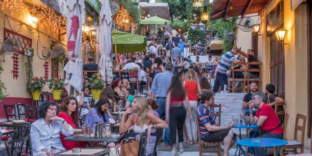 Late afternoon picture of colorful pewople sitting at resaturants taking place at popular Plaka, Athens