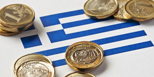 Close-up of a Greek flag and Greek euro coins. Focus is on the Greek euro.Similar