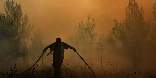 A firefighter works to extinguish a fire east of the Greek capital Athens on August 15, 2017. The army...
