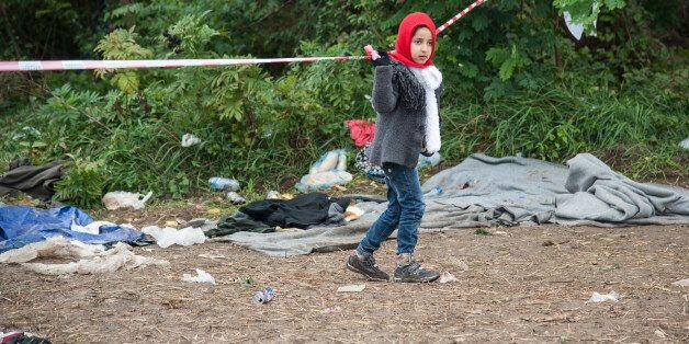SERBIAN-CROATIAN BORDER, BAPSKA, SYRMIA, CROATIA - 2015/09/23: A child on the path leading to the Serbian-Croatian...