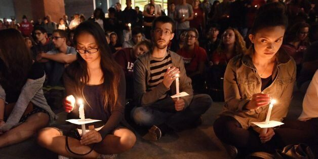 People attend a candlelight vigil at the University of Las Vegas student union October 2, 2017, after...