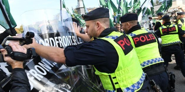 Police officers stop the far-right Nordic Resistance Movement march as it changed the planned route,...