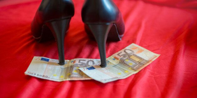 heels on 50 euro banknote on red