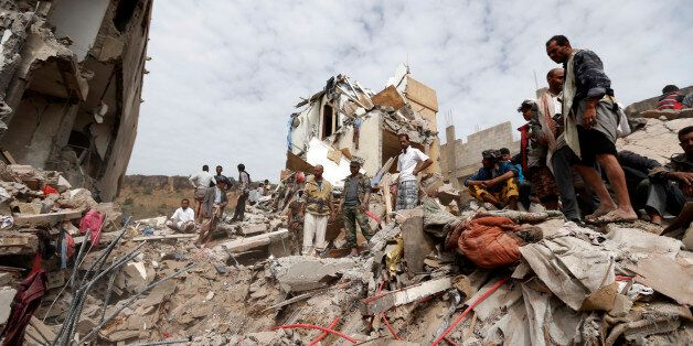 TOPSHOT - Yemenis search under the rubble of a house destroyed in an air strike in the residential southern...
