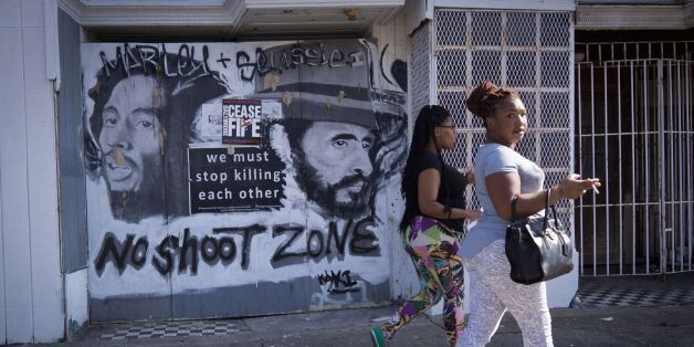 Women walk past a sign with a message to end gun violence in the Sandtown neighborhood of west Baltimore...