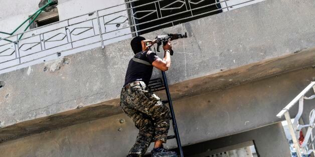 A member of the Syrian Democratic Forces (SDF) climbs up over a balcony as they advance near the central...