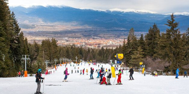 Bansko, Bulgaria - February 11, 2016: Skiers on the slope , ski lift, mountains view and Bansko town