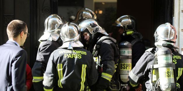Firefighters work to put out a fire in an apartment building in central Paris on July 25, 2017. / AFP...