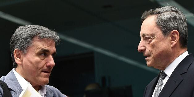Greece's Finance Minister Euclid Tsakalotos (L)speaks with European Central Bank President Mario Draghi...