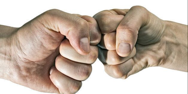 Clash of two fists on white, isolated background. Concept of confrontation, competition