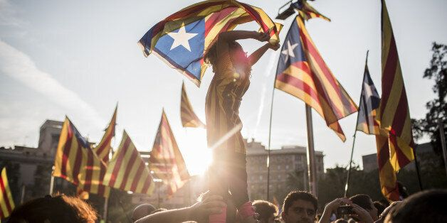 Demonstrators wave Catalan flags while marching through the city to protest against alleged police violence...
