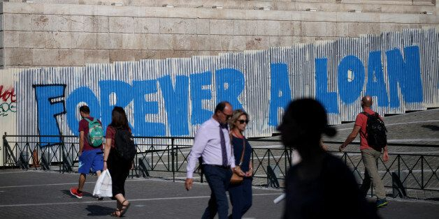 People walk by a graffiti that reads Forever a Loan in Athens city center, Greece, September 7, 2017....