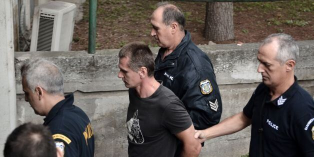 Russian Alexander Vinnik (C) is escorted by police officers as he arrives at a courthouse in Thessaloniki...