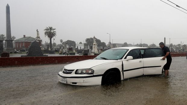 Angel Marshman opens the back door to his flooded car as he stands in floodwaters from Tropical Depression Imelda Wednesday, Sept. 18, 2019, in Galveston, Texas. (AP Photo/David J. Phillip)