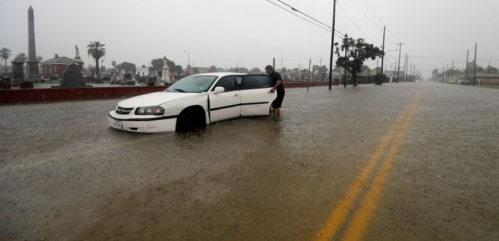 Angel Marshman opens the back door to his flooded car as he stands in floodwaters from Tropical Depression Imelda Wednesday,