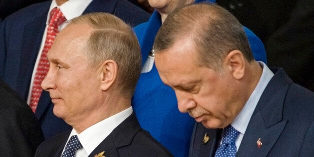 Russian President Vladimir Putin (L) and Turkish President Recep Tayyip Erdogan (R) pose for a family...