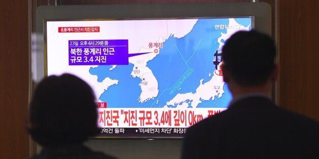 People watch a television news screen showing a map of the epicenter of an earthquake in North Korea,...
