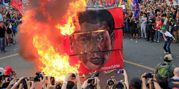 Protesters burn a cube effigy with a face of President Rodrigo Duterte during a National Day of Protest...