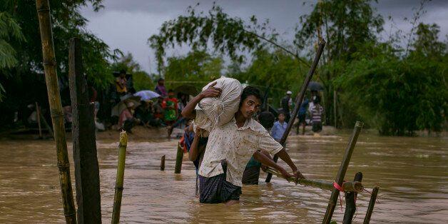 COX'S BAZAR, BANGLADESH - SEPTEMBER 19: Refugees cross a flooded bridge in the Balukhali Rohingya refugee...