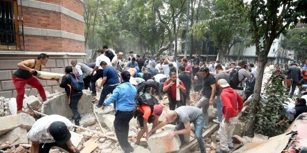 People remove debris of a damaged building after a real quake rattled Mexico City on September 19, 2017...