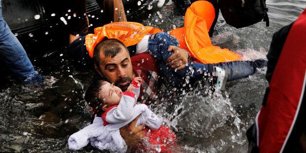 A Syrian refugee holds onto his two children as he struggles to disembark from a raft on the northern...