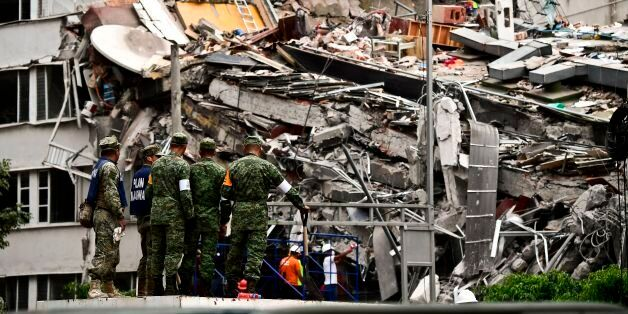Rescuers search for survivors amid the rubble from a building flattened by the 7.1-magnitude quake the...