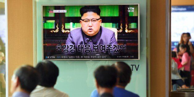 People watch a television news screen showing a picture of North Korean leader Kim Jong-Un delivering...