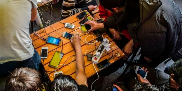 Migrants charge their mobile phones in a restaurant near the central bus station in Belgrade, on March...