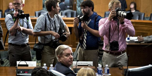 Senator Lindsey Graham, a Republican from South Carolina, bottom center, stays seated during a disruption...