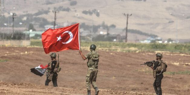 Soldiers holding Turkish and Iraqi flags walk during a joint military exercise near the Turkish-Iraqi...