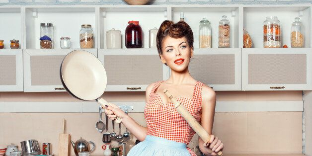 The girl in the kitchen in the hands holding pan and rolling pin.