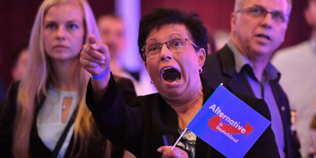 Supporters of the Alternative for Germany (AfD) react after exit poll results were broadcasted on public...