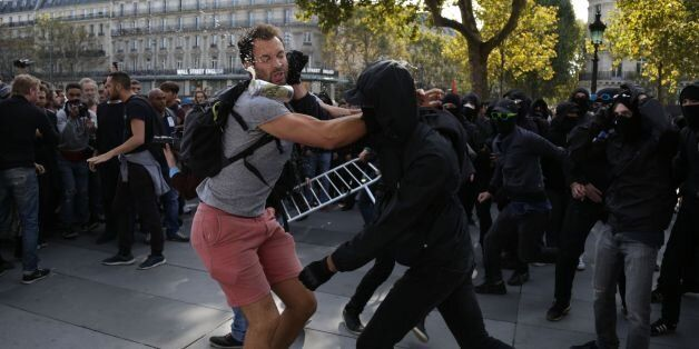 TOPSHOT - A demonstrator tries to prevent a group of balaclava-clad people from trying to take over a...