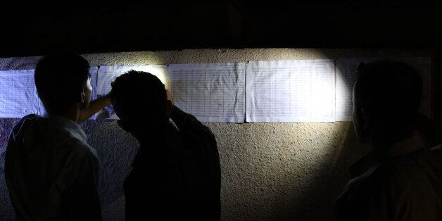 Iraqi Kurds check for their names on the voting lists posted outside a polling station in Arbil, the...