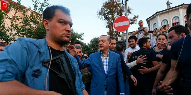 Turkish President Tayyip Erdogan walks through the crowd of supporters protected by bodyguards in Istanbul,...