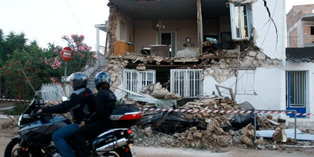 A motorcyclist rides past a destroyed house after a strong earthquake hit Kato Achaia village some 250Km...