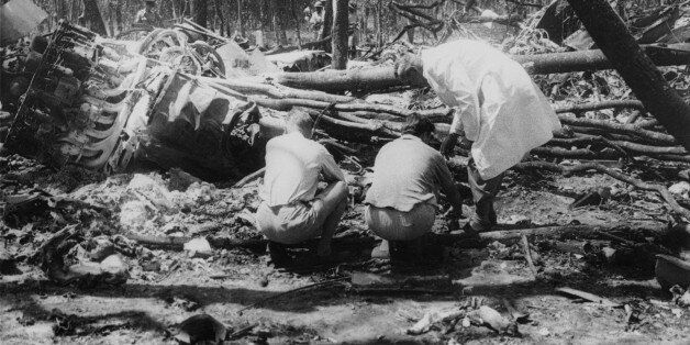 Officials search the crash site after the plane carrying Swedish diplomat Dag Hammarskjold (1905 - 1961),...