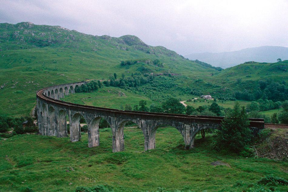 """Apelidado de """"a ponte de Harry Potter"""", o viaduto Glenfinnan, nas Highlands da Escócia, fez parte da rota seguida pelo Expresso de Hogwarts. O carro Ford Anglia de Arthur Weasley sobrevoou o viaduto, em cena que ficou famosa. O trem a vapor dos jacobitas passa regularmente sobre o viaduto, criando uma cena muito potteriana. O passeio no trem a vapor também é uma opção muito popular."""