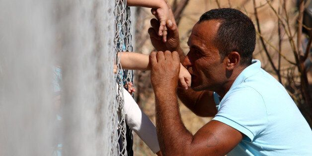 Ammar Hammasho from Syria who lives in Cyprus kisses his children who arrived at the refugee camp in...
