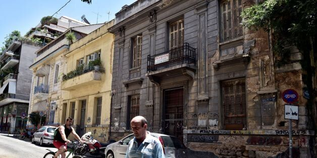 People pass a neoclassical building for sale in one of the oldest districts of Athens on July 7, 2017.A...