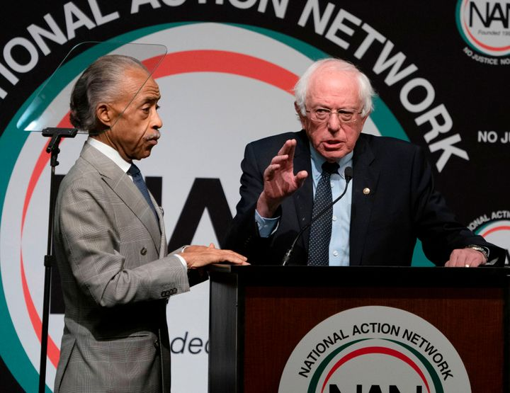 Bernie Sanders, right, speaks at a conference held by Rev. Al Sharpton in April. Sanders' critics say his efforts to focus mo