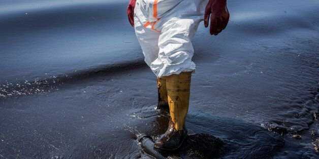 A municipal worker tries to contain the oil spill from the Greek tanker Agia Zoni II, which sank off...