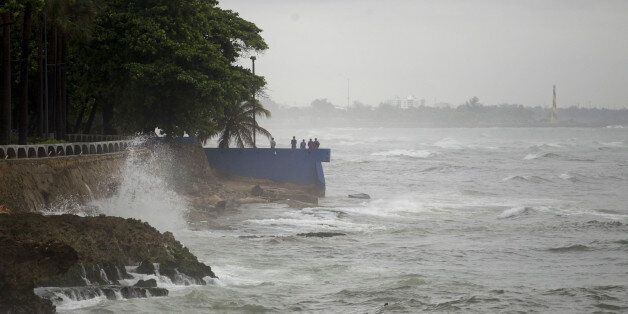 People stand by the sea in the rain in the La Cienaga neighborhood on September 7, 2017, as Hurricane...