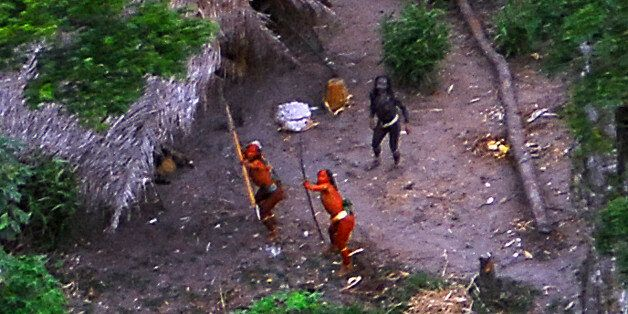 Members of an uncontacted Amazon Basin tribe and their dwellings are seen during a flight over the Brazilian...