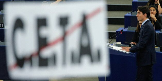 Canada's Prime Minister Justin Trudeau is seen behind a poster with a crossed CETA (Comprehensive Economic...
